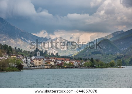 view of the Barcis city on the lakeside surrounding mountains against a dramatic cloudy blue sky background in Valcellina, Pordenone, Italy  #644857078
