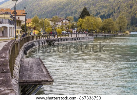 view of the Barcis city on the lakeside surrounding mountains against a dramatic cloudy blue sky background in Valcellina, Pordenone, Italy  #667336750
