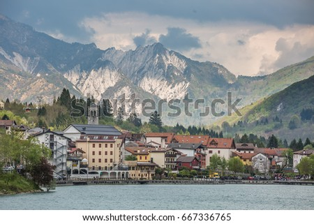 view of the Barcis city on the lakeside surrounding mountains against a dramatic cloudy blue sky background in Valcellina, Pordenone, Italy  #667336765