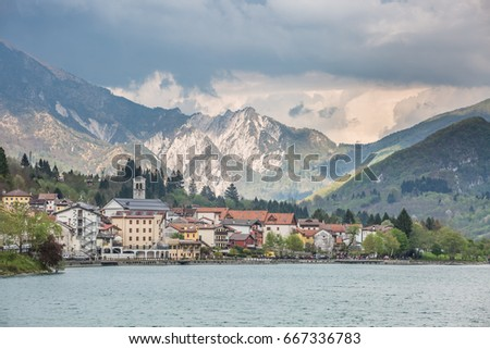 view of the Barcis city on the lakeside surrounding mountains against a dramatic cloudy blue sky background in Valcellina, Pordenone, Italy  #667336783