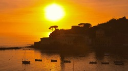 View of the Bay of Silence beach with boats on colorful warm romantic sunset in Sestri Levante, Liguria, Italy