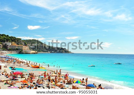 View of the beach in Nice, France, near the Promenade des Anglais. tourists, sunbeds and umbrellas on summer hot day
