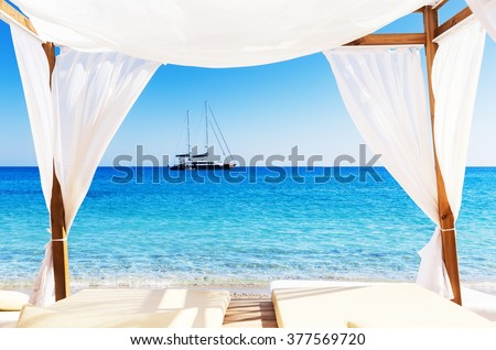 View of the beautiful beach through a Balinese bed