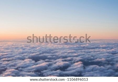 View of the beautiful sky and clouds from the window of the airplane. Sunset sky from the window of the airplane. Wing of an airplane against a beautiful sunset sky.  #1106896013