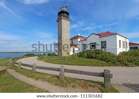 View of the Beavertail Light lighthouse near Jamestown on Conanicut Island, Rhode Island, with a bright blue sky and white clouds