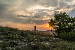 View of the bell tower in matera city, with cloud sky and orange sun during the sunset - holiday,history and nature concept