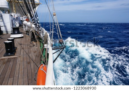 View of the blue sea water from the side of a sailboat with rigging and sails. Tackle barge, sail, masts, yards, deck, ropes, cables #1223068930
