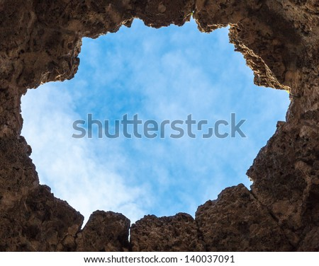View of the blue sky through a hole in the wall