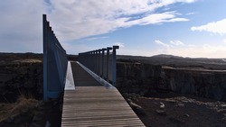 View of the Bridge Between Continents that spans a rock fissure above the Mid Atlantic Ridge (MAR), where the Eurasian and American tectonic plates drift apart, on Reykjanes peninsula, Iceland.