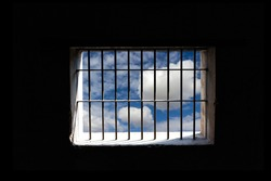 View of the bright blue sky with white clouds through a window bars. Concept background of imprisonment and freedom