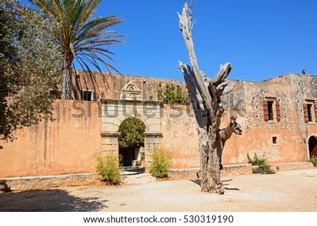 View of the bullet tree with the entrance to the refectory courtyard to the rear at Arkadi Monastery, Arkadi, Crete, Greece, Europe. #530319190