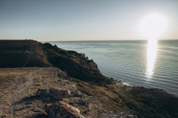 view of the calm black sea and cliffs during the start of sunset