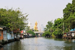 View of the canal with bronze buddha statue in meditation posture height 69 meters of Wat Paknam Phasi Charoen temple as a backdrop.