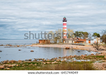 View of the cape on the coast with the old lighthouse in red and white stripes #645744049