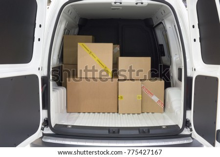 View of the cargo area of light commercial vehicle. Russian text on yellow adhesive tape of the box: First class mail. Russian red text on the white adhesive tape: Fragile.
