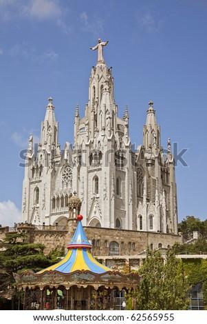 view of the cathedral in Barcelona Spain and child carousel sunny day.  Templo del Sagrado Corazn de Jesus, Cim del Tibidabo