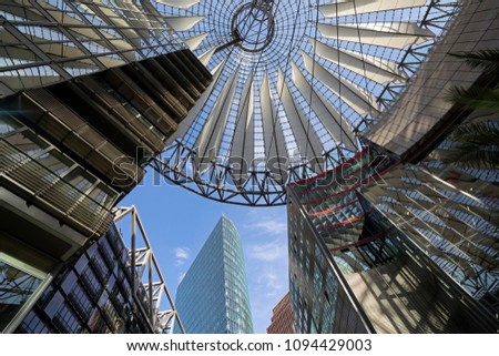 View of the ceiling and the buildings of an arcade with a tower and the sky in the background #1094429003