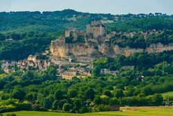 View of the Château de Beynac, a fortified clifftop castle overlooking the River Dordogne, and the Beynac-et-Cazenac village classified as one of the most beautiful villages of France in summer.