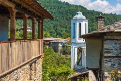 View of the church and the old traditional houses in the architectural reserve of the village of Dolen, Bulgaria.