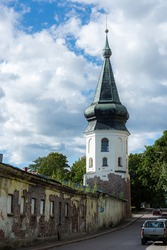 View of the city hall tower in the old part of Vyborg. In the foreground are the ruins of a former artillery barracks.