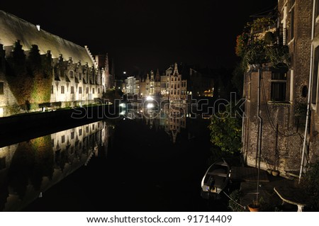 View of the city of Ghent in the evening across one of the many canals traversing it.