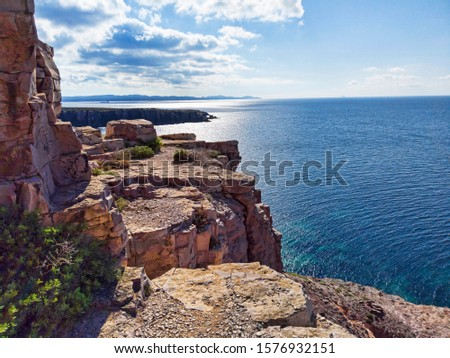 View of the coast line from the cliff overlooking the blue sea with scenic panorama of the beautiful Saint Peter island in Sardinia region, Italy