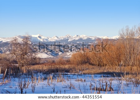 View of the Colorado Indian Peaks area of the Rocky Mountain Continental Divide from the prairie east of Boulder, in early morning bright sunlight in winter