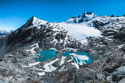 View of the colorful Brewster Glacier and Blue Lake with snow from the top of Amstrong National Park, Mount Aspiring, New Zealand.