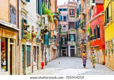 View of the colorful Venetian houses with some visitors walking by in Venice, Italy.