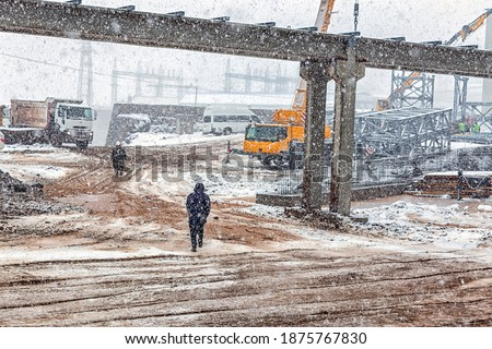View of the construction site with snowy weather. Construction is a general term meaning the art and science to form objects, systems, or organizations.