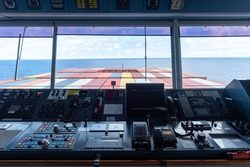 View of the control console on the navigational bridge of the cargo container ship.