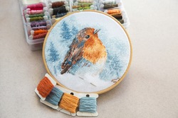 view of the cross stitch process in the hoop multicolored bird, white canvas, floss threads on bobbins, needle, needlework and cross stitch concept
