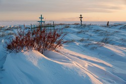 View of the crosses in the snowy tundra on the coast of the frozen sea. An old cemetery in the far North of Russia in the Arctic. Snow-covered graves. Cold winter weather. Chukotka, Siberia, Russia.