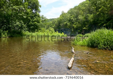 View of the Current River flowing through lush greenery and forest trees in the Ozarks, Missouri, USA in a tranquil scenic landscape