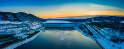 View of the dam of a hydroelectric power station, in Siberia on the river in winter, aerial photography