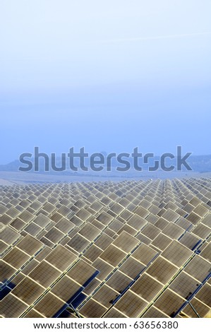 view of the dawn of a solar field with hills in the background