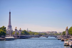 View of the Eiffel Tower from the Seine, with a view of a bridge in panoramic view.