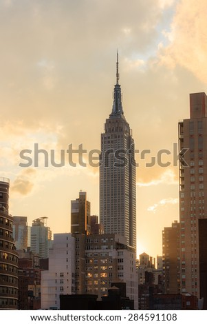 View of the Empire state building at sunset, golden orange clouds in the background - April 22, 2015, midtown Manhattan, New York city, NY, USA