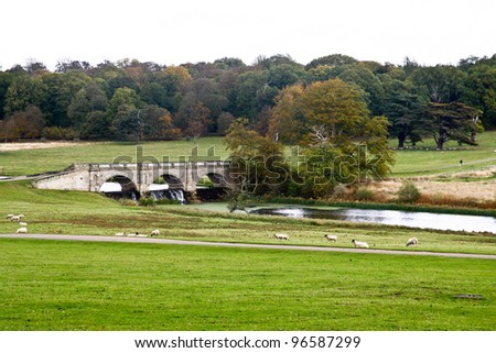view of the english countryside with trees and a lush grass with a river flowing through the middle and a bridge crossing it.