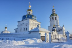 View of the ensemble of churches with golden domes against the blue sky on a frosty winter day. Holy Znamensky Abalaksky Monastery 1636 - construction of the first temple