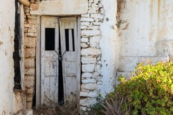 View of the facade of a ruined building in Chora. Locked door with a padlock . Folegandros Island, Greece.