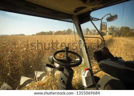 View of the field of corn from the cab of a combine harvester on a sunny day. Workplace of a combine operator. Theme is agricultural and agriculture.