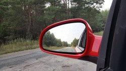 View of the forest and the road to the side mirror of my car