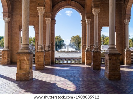 View of the fountain in the Plaza de España in Seville seen from the main building (Andalusia, Spain). Historic building with pillars and arches that has become the most emblematic place in the city. Foto stock ©