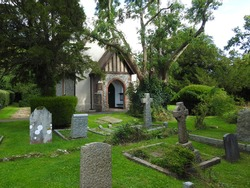 View of the front part of a small church with trees, greenery and a cemetery