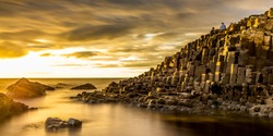 View of the Giant's Causeway in Northern Ireland at sunset with a golden light and dramatic sky