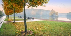 View of the golden autumn trees of Tsaritsyno Park in Moscow on the banks of the pond and benches in the early morning