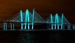 View of the Governor Mario M. Cuomo Bridge (new Tappan Zee Bridge) at night from Pierson Park in Tarrytown, NY.   The bridge is colored in a beautiful blue green hue with a fiery night sky.