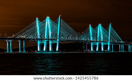 View of the Governor Mario M. Cuomo Bridge (new Tappan Zee Bridge) at night from Pierson Park in Tarrytown, NY.   The bridge is colored in a beautiful blue green hue with a fiery night sky. Stockfoto ©