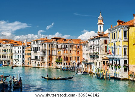 View of the Grand Canal with gondolas and colorful facades of old medieval houses from the Rialto Bridge in Venice, Italy. Venice is a popular tourist destination of Europe.